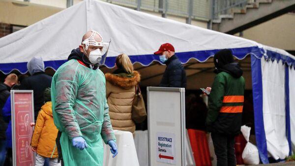 Медицинский работник у больницы, где проходит добровольное экспресс-тестированию на коронавирус, в Праге