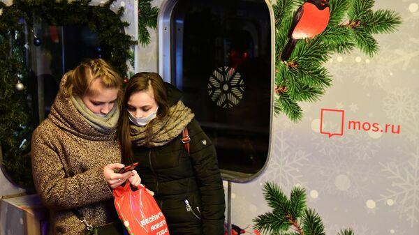 Пассажиры в вагоне новогоднего поезда серии Ёж Московского метрополитена