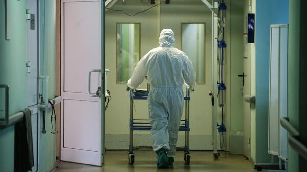 Медик в защитном противоэпидемическом костюме в коридоре Новосибирской областной клинической больницы