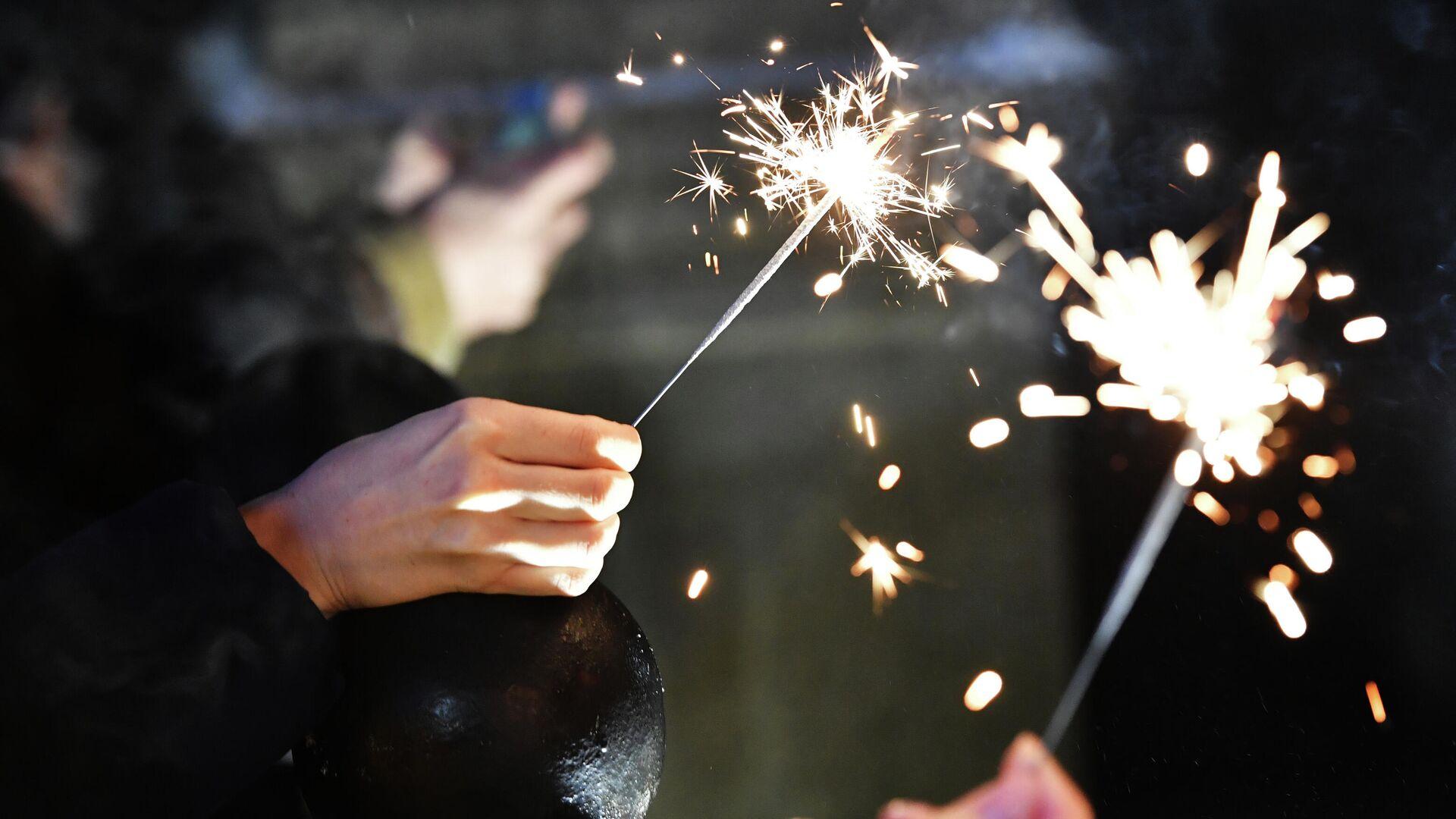 Бенгальские огни в руках людей, празднующих Новый год - РИА Новости, 1920, 30.12.2020