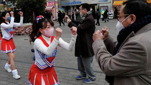 Чирлидеры подбадривают людей во врем усиления антикоронавирусных мер в Токио, Япония