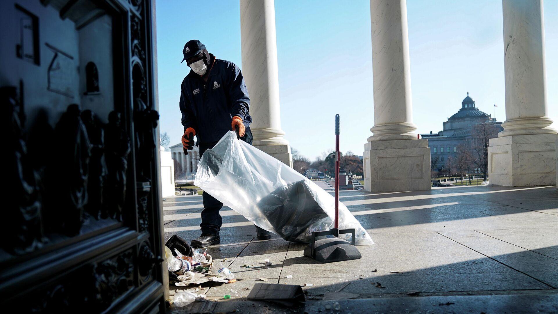 Рабочий убирает мусор возле Капитолия США через день после штурма сторонниками президента США Дональда Трампа - РИА Новости, 1920, 07.01.2021