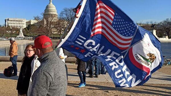 Мужчина с флагом сторонников Дональда Трампа на Капитолийском холме в Вашингтоне
