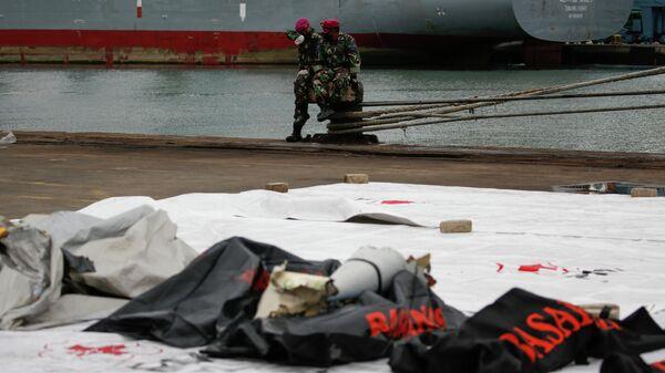 Индонезийские солдаты перед  обломками самолета Sriwijaya Air, который упал в море недалеко от Джакарты