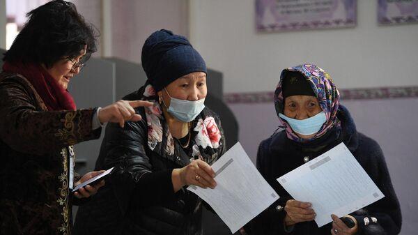 Женщины с бюллетенями на одном из избирательных участков в Бишкеке во время голосования на досрочных выборах президента Кыргызской Республики