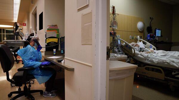 Пациент лежит на кровати в отделении COVID-19 в Медицинском центре Святого Креста Провиденса в районе Мишн-Хиллз в Лос-Анджелесе