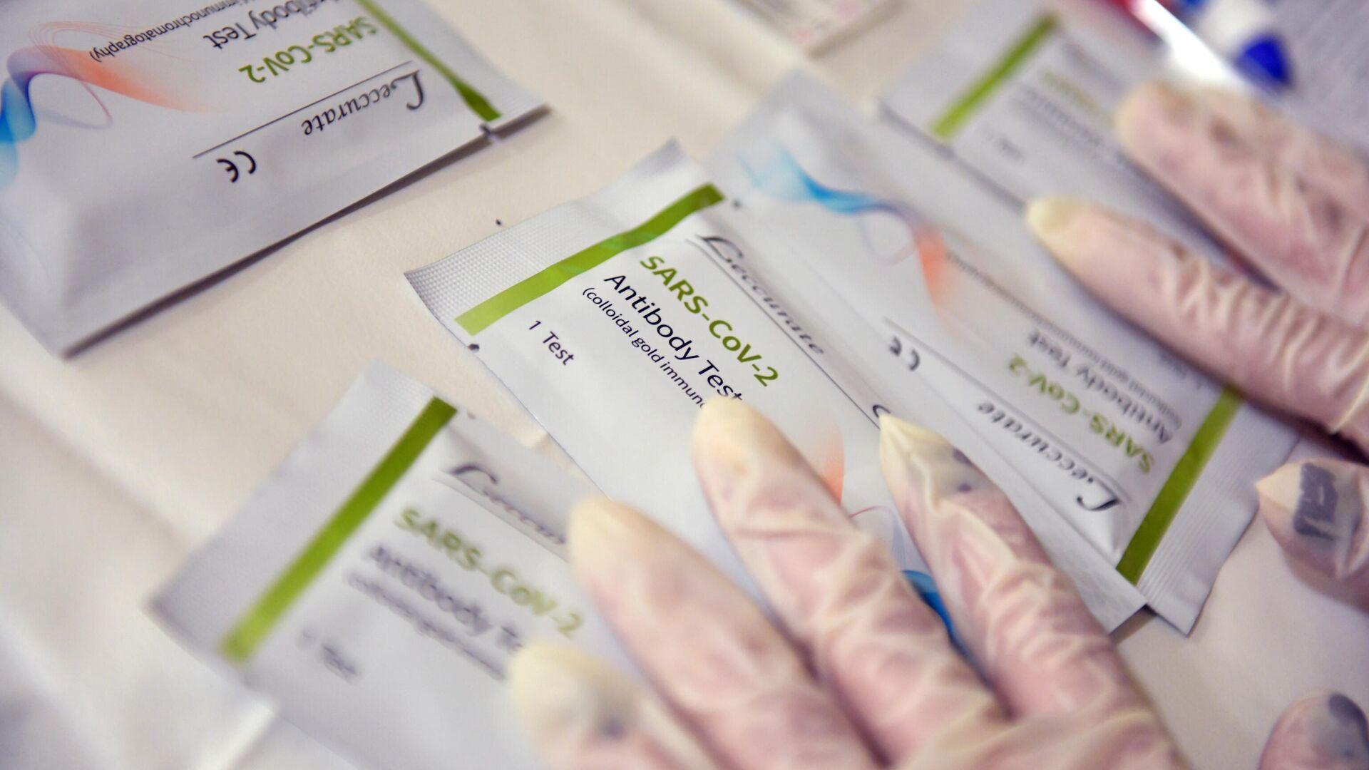Медицинский работник держит в руках тест на антитела в мобильном многопрофильном госпитале для больных коронавирусом в Абхазии - РИА Новости, 1920, 29.01.2021