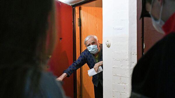 Пожилой мужчина в дверях своей квартиры