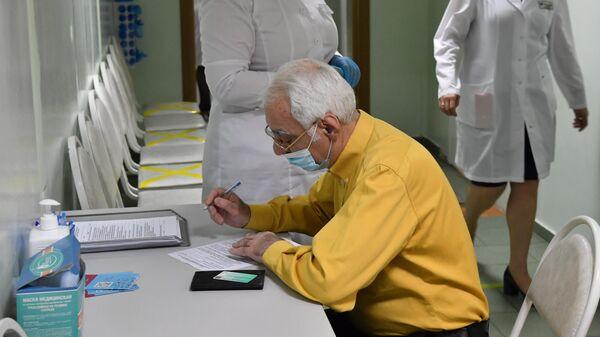 Медработники и пожилой пациент перед вакцинацией от коронавируса COVID-19 вакциной Спутник V в Москве
