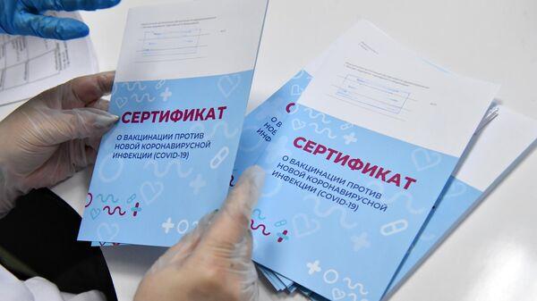 Медработник с сертификатами о вакцинации от новой коронавирусной инфекции COVID-19