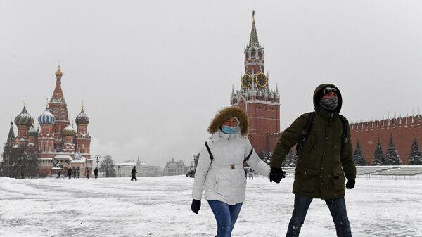 Прохожие на заснеженной Красной площади в Москве