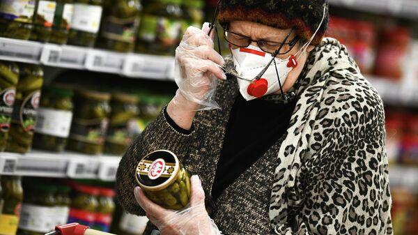 Покупатель выбирает маринованные огурцы в гипермаркете Ашан