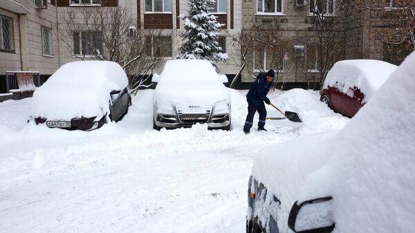 Сотрудник коммунальной службы чистит от снега дорогу во время снегопада в Москве