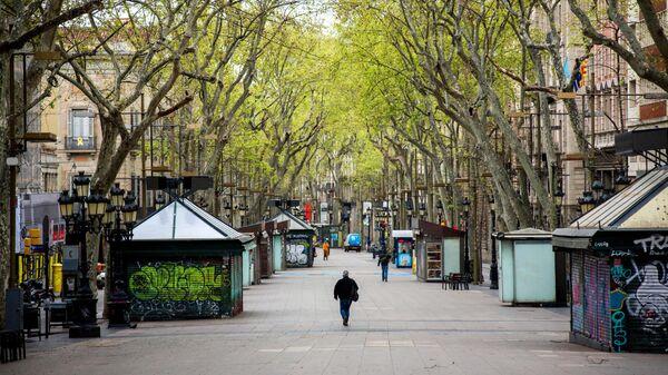 Мужчина в защитной маске идет по пустой пешеходной улице Рамбла в центре Барселоны