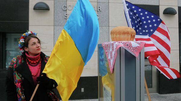 Женщина с флагом Украины у посольства США в Киеве