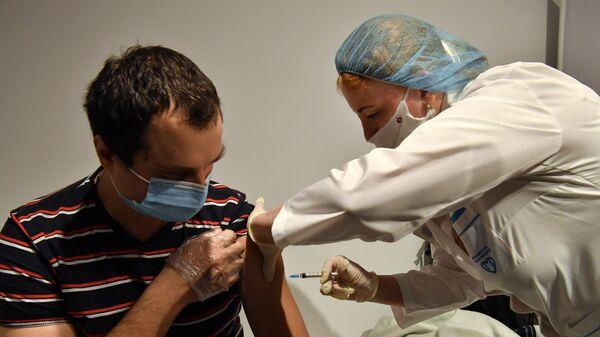 Мужчине делают прививку от коронавируса