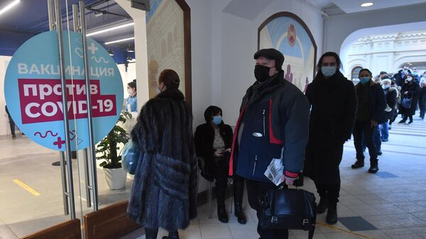 Люди возле пункта вакцинации от коронавируса в ГУМе в Москве