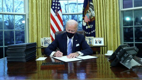 Президент США Джо Байден подписывает документы в в Овальном кабинете Белого дома в Вашингтоне после церемонии инаугурации