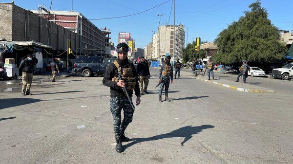 Сотрудники иракских правоохранительных органов недалеко от места теракта в Багдаде
