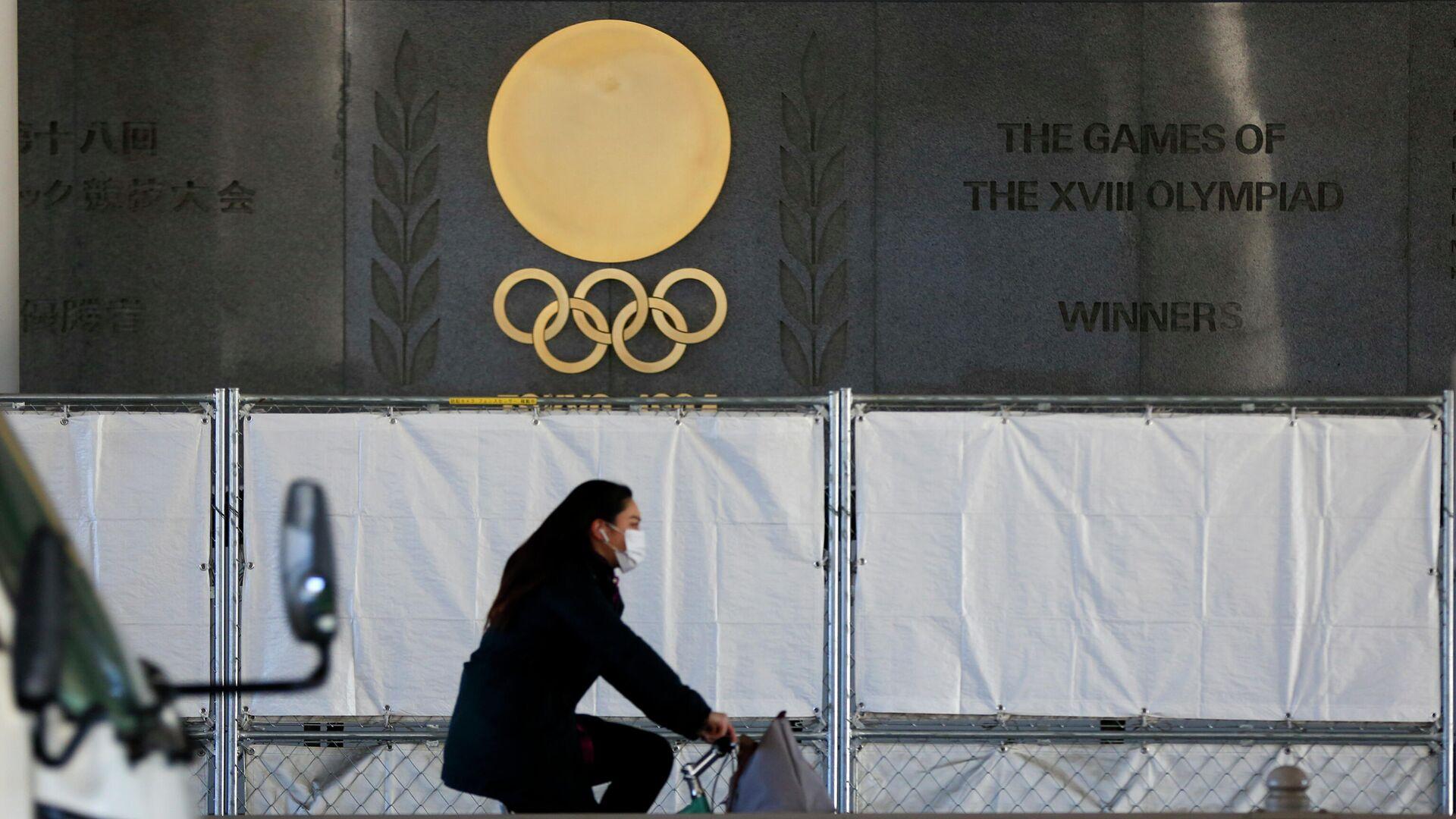 Девушка проезжает на велосипеде мимо Национального стадиона в Токио  - РИА Новости, 1920, 22.01.2021