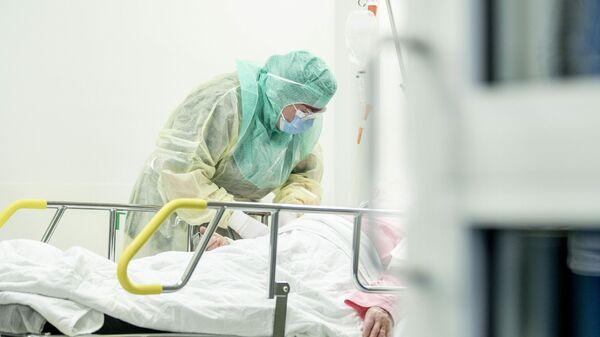 Медсестра в защитном костюме берет образец крови пациента для анализа на коронавирус Covid-19, в университетской больнице Турку
