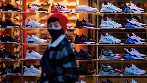 Женщина проходит мимо витрины с кроссовками в Берлине