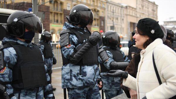 Женщина разговаривает с сотрудниками правоохранительных органов на Тверской улице в Москве