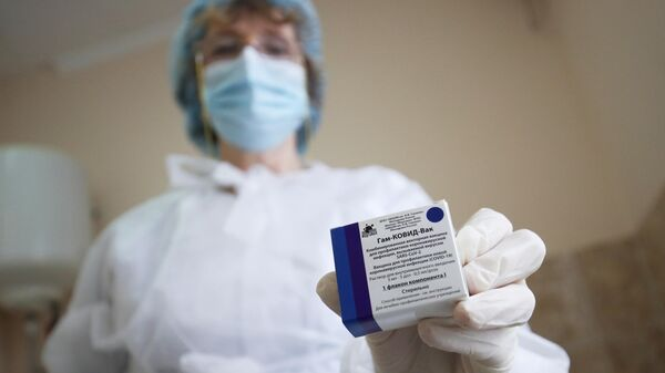 Медицинский сотрудник держит в руке вакцину от COVID-19 Спутник-V