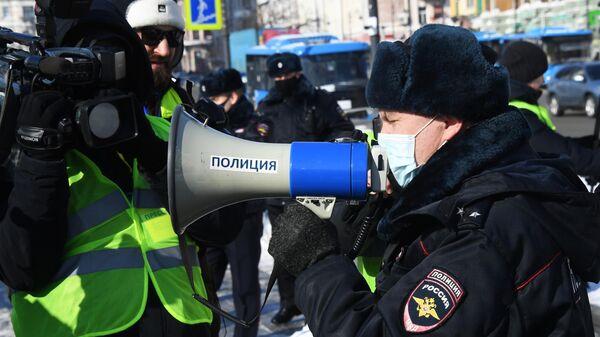 Сотрудник правоохранительных органов и журналисты во время несанкционированной акции протеста во Владивостоке