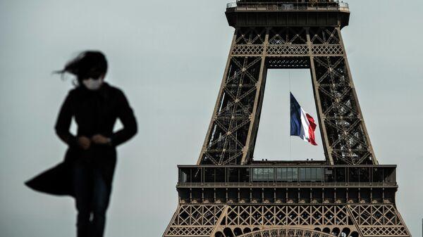 Женщина в маске на фоне Эйфелевой башни с флагом Франции