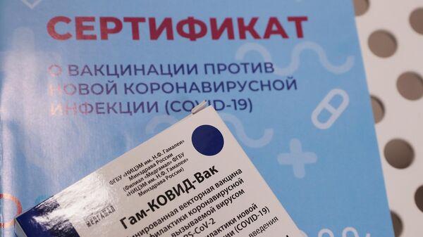 Сертификат о вакцинации от COVID-19 и упаковка российского препарата Гам-Ковид-Вак (Спутник V) в специализированном пункте в торговом центре Калейдоскоп в Москве