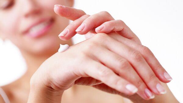 Девушка наносит крем на руки