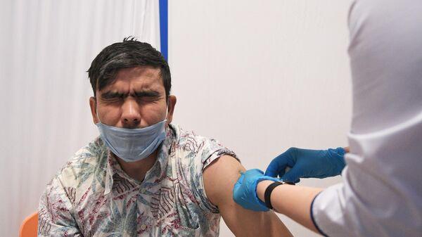 Медик выездной бригады вакцинирует мужчину российским препаратом от COVID-19 Гам-Ковид-Вак