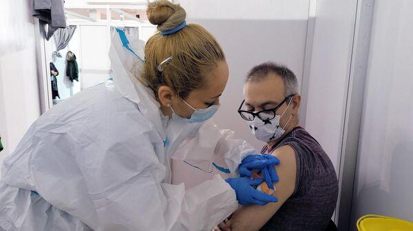 Мужчине делают прививку российской вакциной против COVID-19 Спутник V (Гам-КОВИД-Вак) в Белграде
