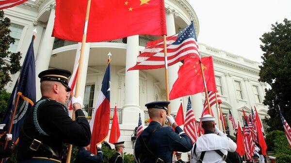 Военнослужащие США с флагами США и Китая на фоне Белого дома в Вашингтоне
