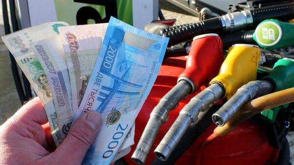 Деньги на оплату топлива в руке мужчины на АЗС сети ННК в Хабаровске
