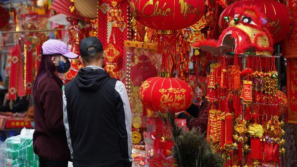 Посетители на рынке новогодних сувениров и украшений для дома на центральной улице Ханоя