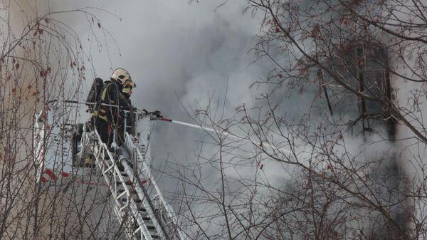 Сотрудники пожарной службы тушат пожар в жилом доме в поселке Мосрентген в Новой Москве