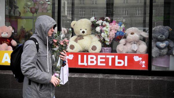 Молодой человек проходит мимо витрины магазина с сувенирной продукцией ко Дню Святого Валентина
