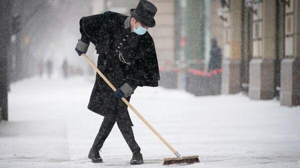 Портье отеля Adlon чистит улицу после снегопада в Берлине, Германия