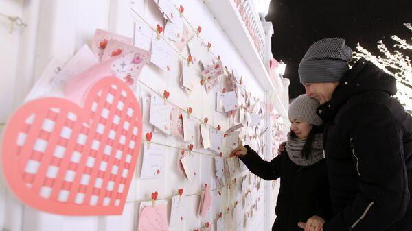 Молодые люди возле Стены признаний на Кремлевской набережной, где открыли Аллею влюбленных в городе Казань