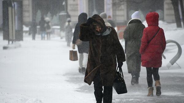Прохожие во время снегопада в центре Москвы