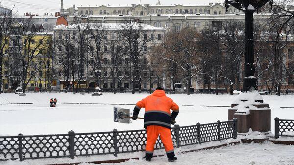 Сотрудник коммунальной службы убирает снег на Патриарших прудах в Москве