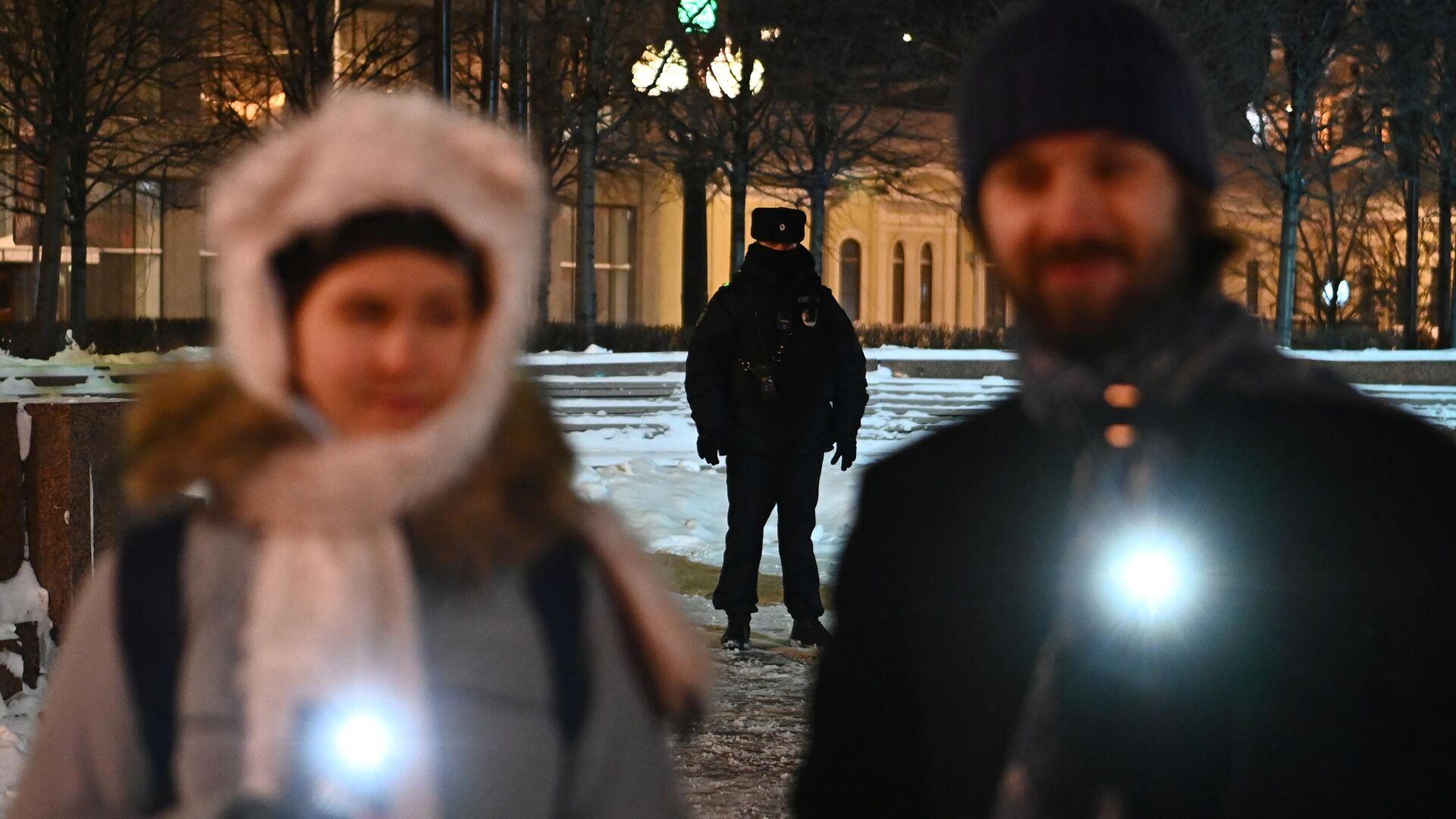 Сотрудник полиции наблюдает за порядком во время флешмоба с включенными фонариками в Москве - РИА Новости, 1920, 15.02.2021