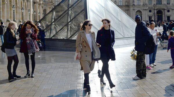 Девушки у стеклянной пирамиды Лувра во дворе Наполеона в Париже