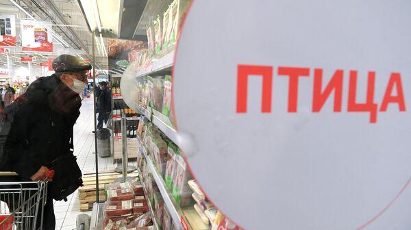 Покупатель в мясном отделе гипермаркета Ашан в Москве