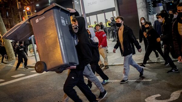 Участники акции протеста в поддержку рэпера Пабло Аселя, приговоренного к девяти месяцам заключения за оскорбление монархии и прославление леворадикального терроризма, на одной из улиц в Барселоне