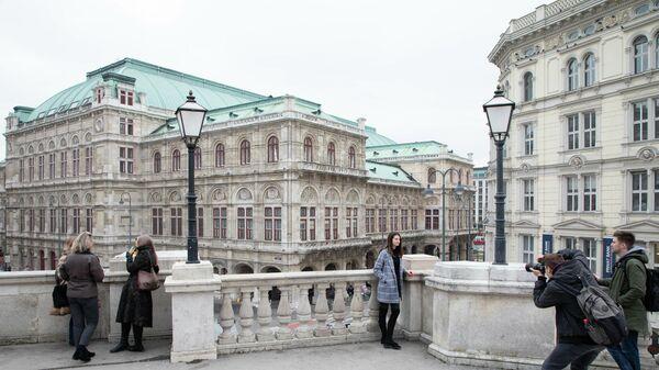 Девушка фотографируется на фоне здания Венской государственной оперы
