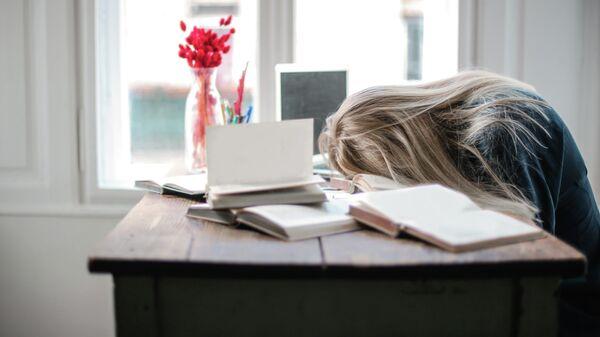 Молодая женщина спит за рабочим столом