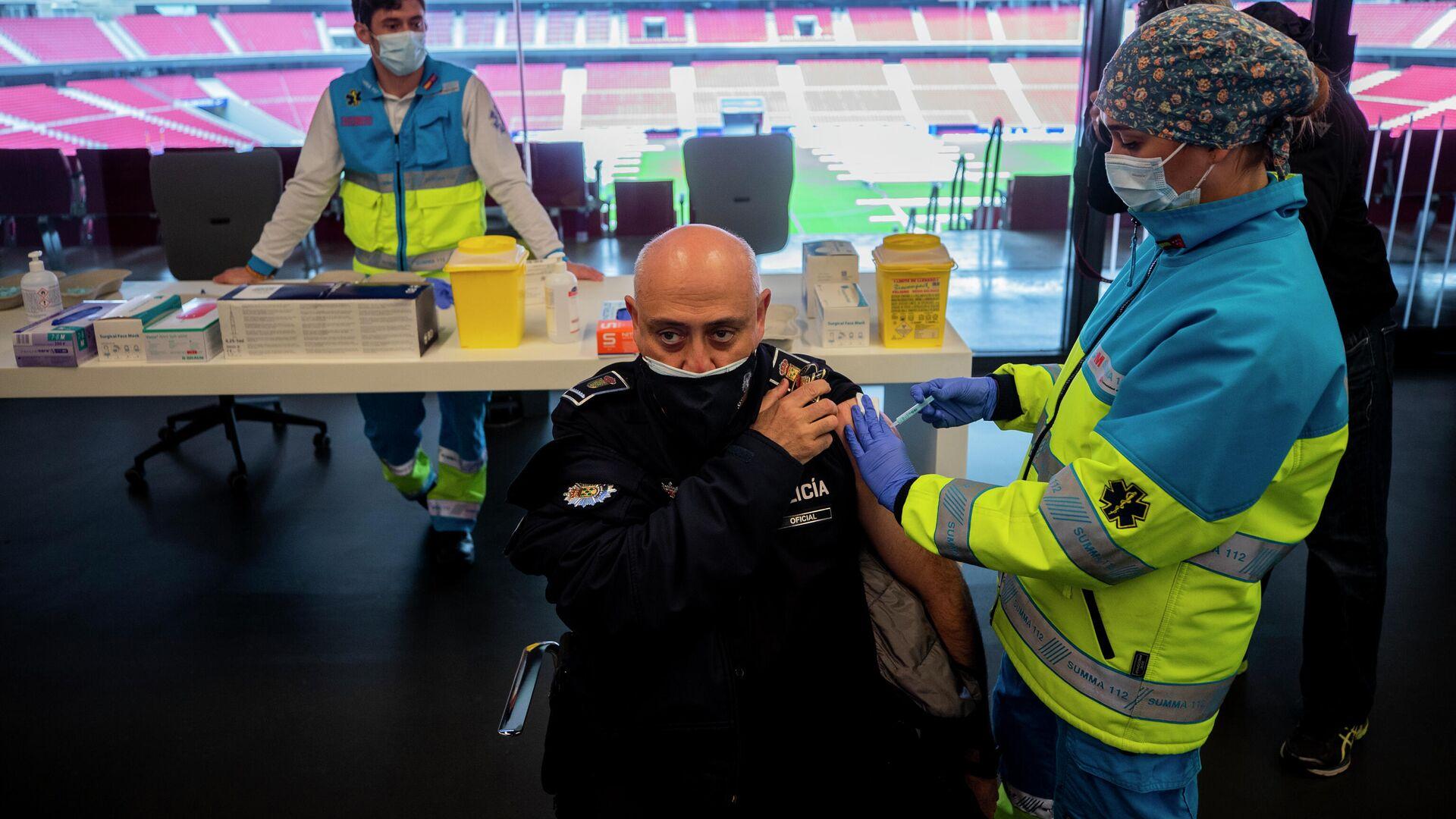 Полицейский во время инъекции вакцины AstraZeneca против COVID-19 в Мадриде - РИА Новости, 1920, 11.03.2021